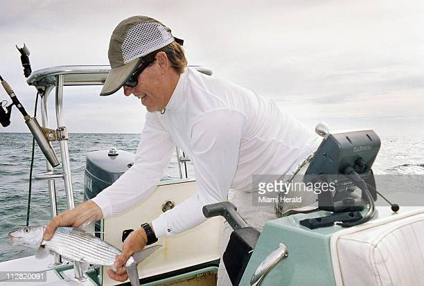Captain Carl Ball prepares to release a bonefish near Crandon Beach Florida August 26 2010