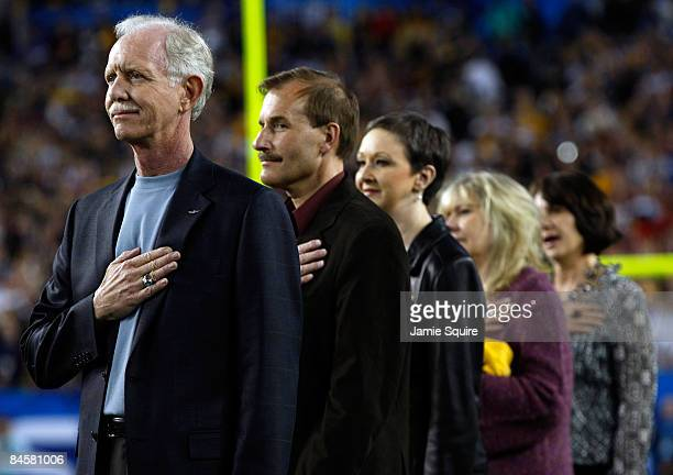 Captain Chesley B. Sullenberger III and the US Airways Flight 1549 crew stand on the field as singer Jennifer Hudson performs the National Anthem...