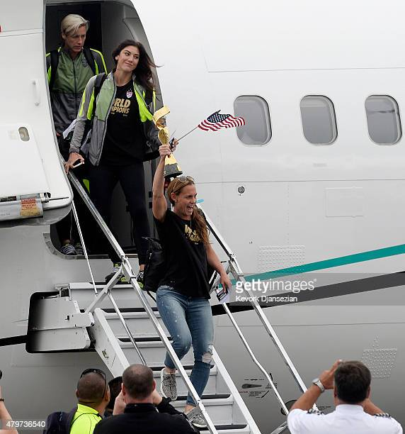Captain Christie Rampone holds the FIFA Women's World Cup trophy as she walks off the plane followed by goalkeeper Hope Solo and forward Abby Wambach...