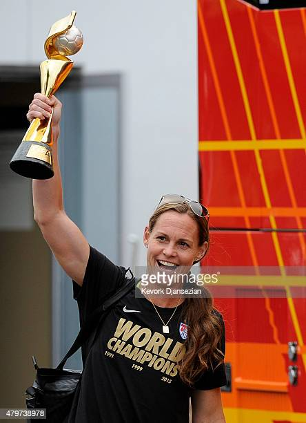 Captain Christie Rampone holds the FIFA Women's World Cup trophy as she walks to the bus after arriving at Los Angeles International Airport July 6...