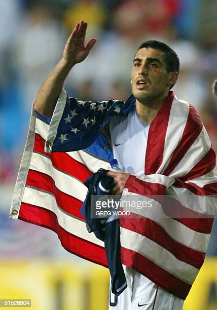USA captain Claudio Reyna drapes himself in an American flag as he walks off the pitch 21 June 2002 at the Munsu Football Stadium in Ulsan during...