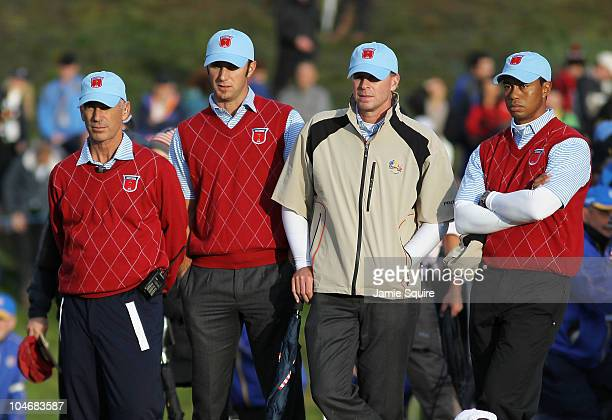 Captain Corey Pavin waits alongside Dustin Johnson, Steve Stricker and Tiger Woods on the 18th green during the Fourball & Foursome Matches during...