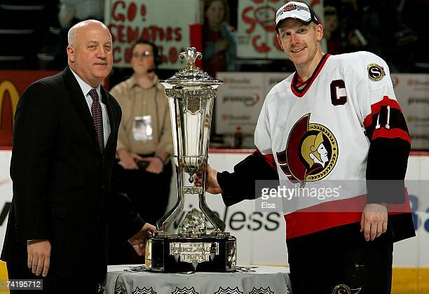 Captain Daniel Alfredsson of the Ottawa Senators poses with the Prince of Wales trophy and Deputy Commissioner of the NHL Bill Daly after the...