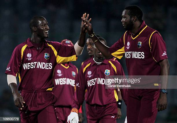 Captain Darren Sammy of West Indies celebrates with team mate Sulieman Benn after taking the wicket of Captain Peter Borren of the Netherlands during...
