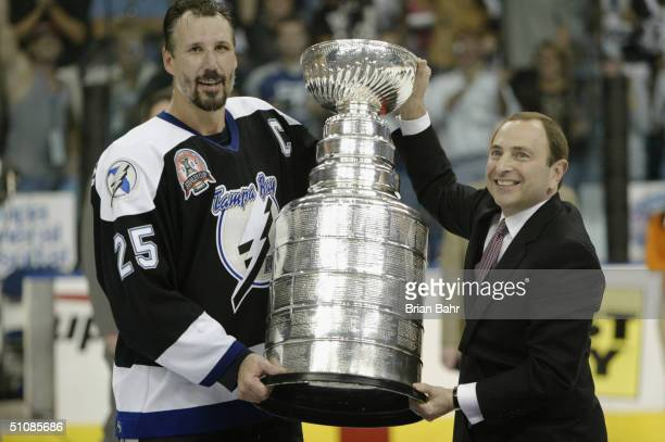 Captain Dave Andreychuk of the Tampa Bay Lightning is presented with the Stanley Cup by NHL Commissioner Gary Bettman after the victory over the...