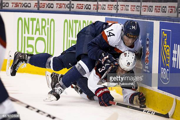 Captain defenseman Erik Cernak of Team Slovakia falls on top of defenseman Jack Ahcan of Team United States in a preliminary round Group B game...