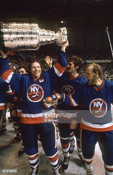 Captain Denis Potvin of the New York Islanders hoists the Stanley Cup as teammate Butch Goring celebrates after winning the 1982 Stanley Cup Finals...