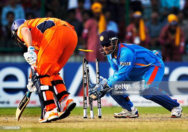 Captain MS Dhoni of India assists in the run out of Bradley Kruger of the Netherlands off the throw from Virat Kohli during the 2011 ICC Cricket...