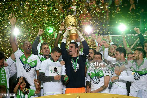 Captain Diego Benaglio of VfL Wolfsburg lifts the trophy with team mates to celebrate victory after the DFB Cup Final match between Borussia Dortmund...