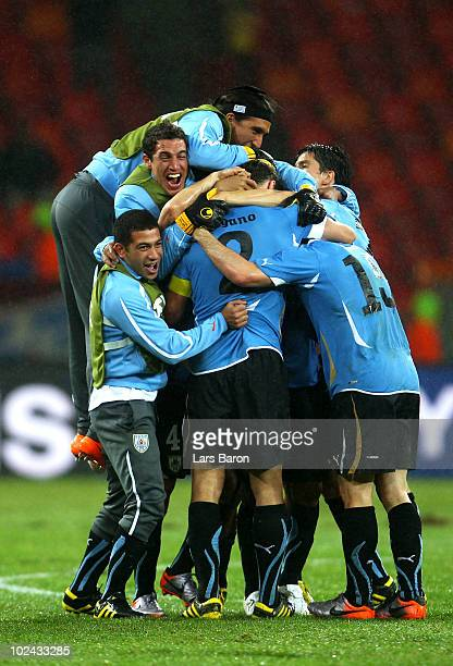 Captain Diego Lugano of Uruguay celebrates victory with team mates following the 2010 FIFA World Cup South Africa Round of Sixteen match between...