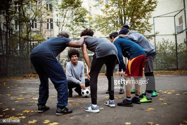 captain discussing with team huddling on street - team captain stock pictures, royalty-free photos & images