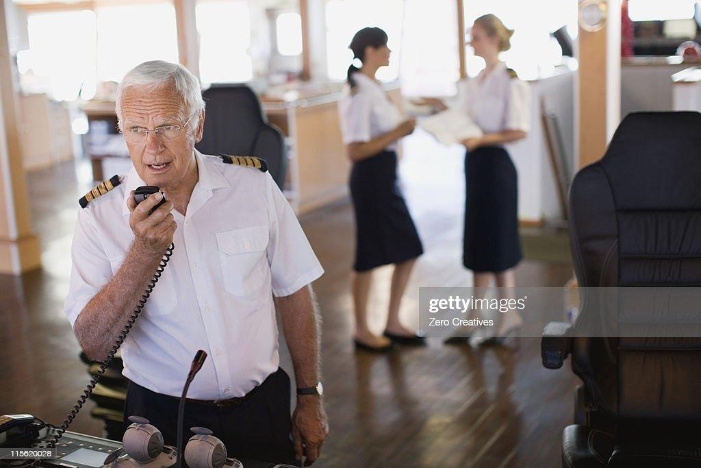 Captain doing a radio message : Stock Photo