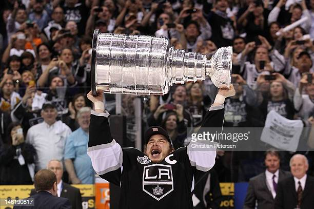 Captain Dustin Brown of the Los Angeles Kings holds up the Stanley Cup after the Kings defeat the New Jersey Devils 61 to win the Stanley Cup in Game...