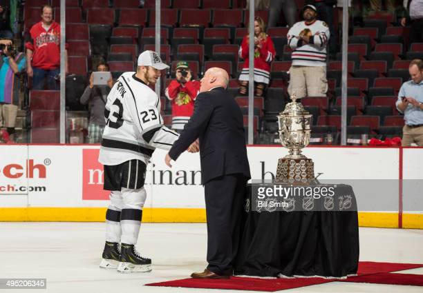 Captain Dustin Brown of the Los Angeles Kings is presented the Clarence S Campbell Bowl by deputy commissioner Bill Daly after the Kings defeated the...