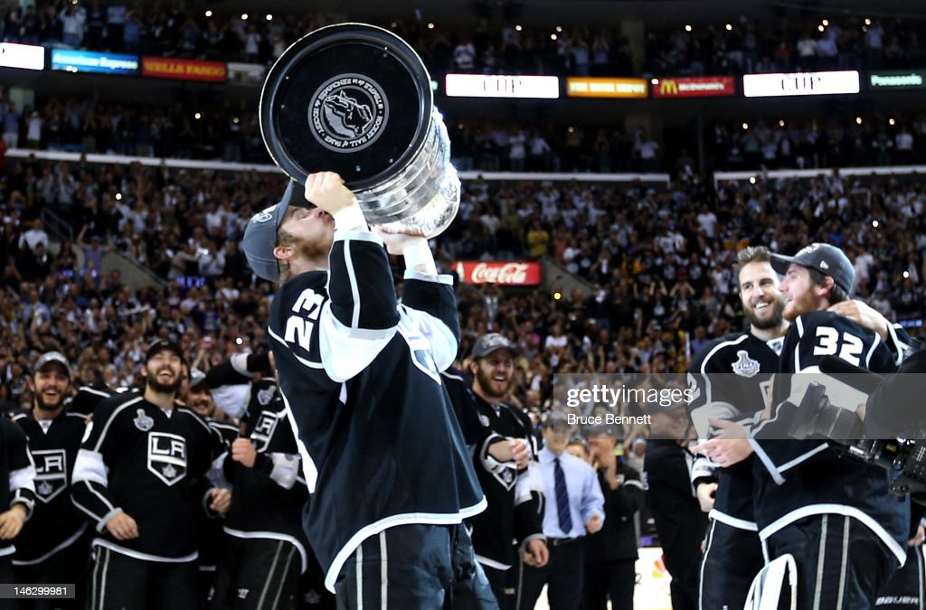 Captain Dustin Brown #23 of the Los Angeles Kings kisses the Stanley Cup as Jonathan Quick #32 and Simon Gagne #12 hug after the Kings defeated the New Jersey Devils 6-1 to win the Stanley Cup final series 4-2 after Game Six of the 2012 Stanley Cup Final at Staples Center on June 11, 2012 in Los Angeles, California.