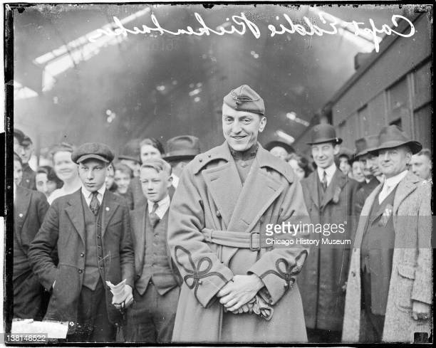 Captain Eddie Rickenbacker standing in a train station with large crowd in background Chicago Illinois 1919