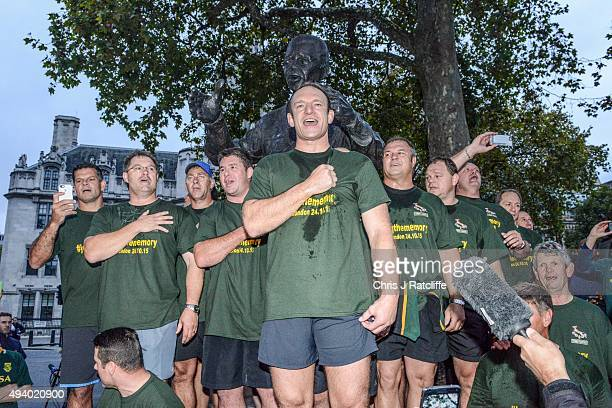 Captain Francois Pienaar and the 1995 South African Rugby World Cup winning squad lead fans in a rendition of their national anthem by a statue of...