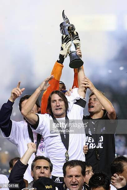 Captain Gabriel Caballero of Pachuca holds up the SuperLiga trophy overhead after they defeated the Los Angeles Galaxy 43 on penalty kicks after the...
