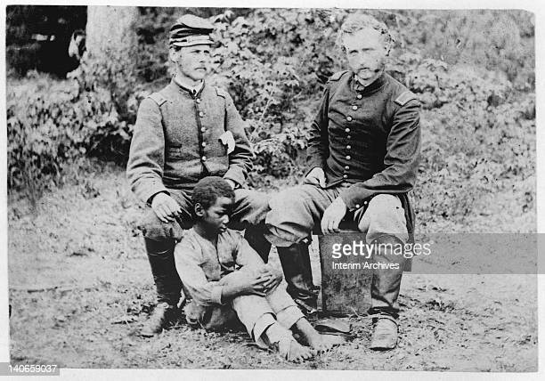Captain George Armstrong Custer of the 5th Cavalry sits with a Confederate prisoner Lieutenant James B Washington and his slave in Fair Oaks VA 1862