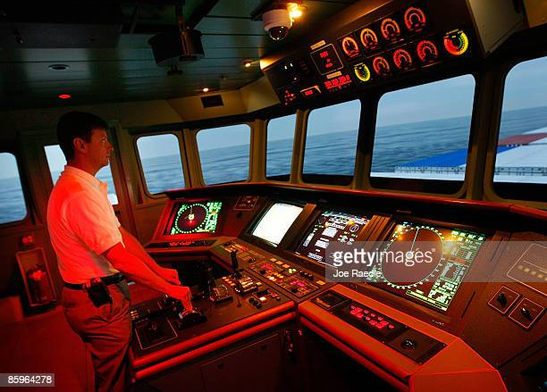 Captain Gerard Pannell keeps an eye on a cargo ship's bridge controls during a demonstration of how they use simulators at the Simulation Training...