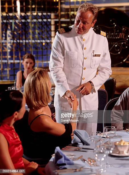 captain greeting two woman  in cruise ship restaurant - team captain stock pictures, royalty-free photos & images