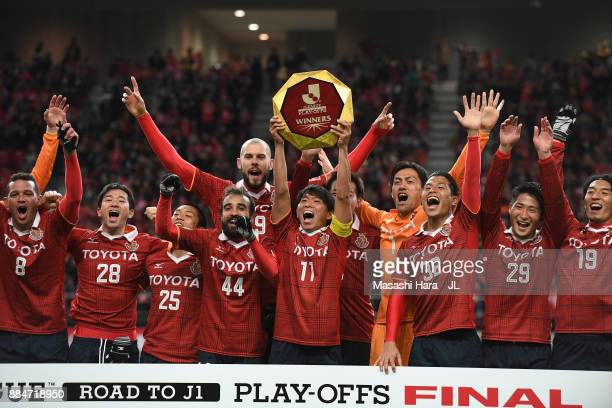Captain Hisato Sato of Nagoya Grampus lifts the trophy as they celebrate the promotion to the J1 after the JLeague J1 Promotion PlayOff Final between...