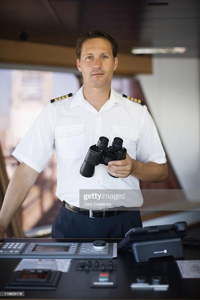 Captain holding binoculars in his hands : Stock Photo