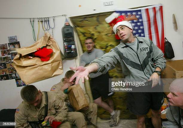 A captain in the 82nd Airborne Division's 1504th 'Red Devils' unit tosses a package to one of his soldiers December 24 2003 in Camp Mercury near the...
