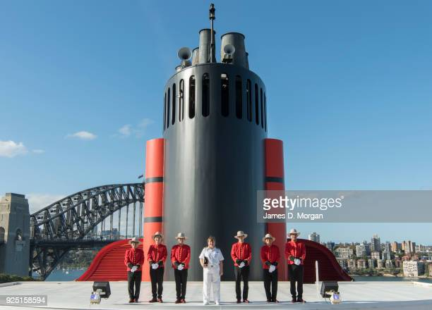 Captain Inger Klein Thorhauge with Cunard's famous Bellboys wearing RMWilliams boots and Akubra hats in front of the funnel of Queen Elizabeth on...