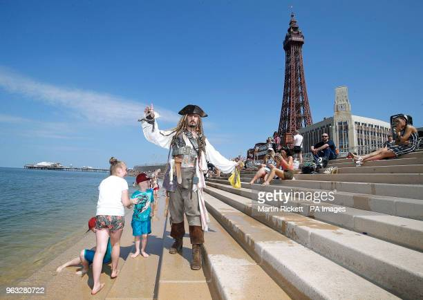 A Captain Jack Sparrow impersonator walks along Blackpool seafront as Britons could see the hottest day of the year this Bank Holiday Monday