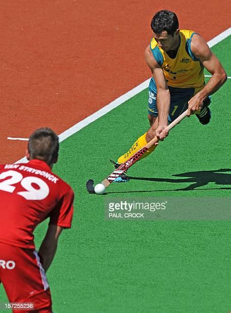 Captain Jamie Dwyer of Australia rushes at Belgian defender Elliot van Strydonck during their men's hockey match at the Champions Trophy in Melbourne...