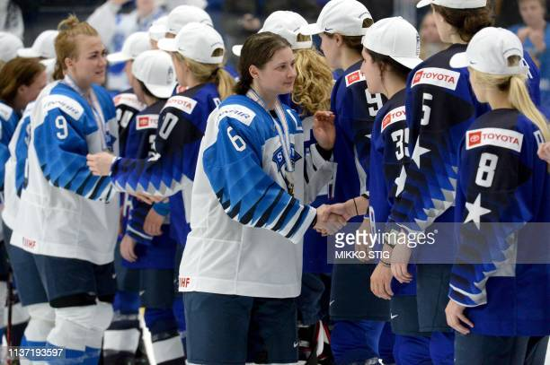 Captain Jenni Hiirikoski of Finland followed by Venla Hovi leads her players to congratulate US players for their 21 shootout victory after the IIHF...