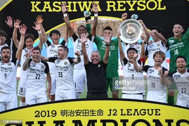 Captain Jiro Kamada of Kashiwa Reysol lifts the trophy next to Nelsinho Baptista Coach of Kashiwa Reysol as they celebrate winning the J2 League...