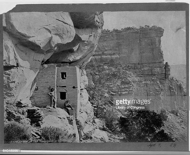 """""""Captain"""" John Moss and Ernest Ingersoll, a reporter for the New York Tribune, stand next to the ruins of cliff dwellings in the Canyon of the..."""