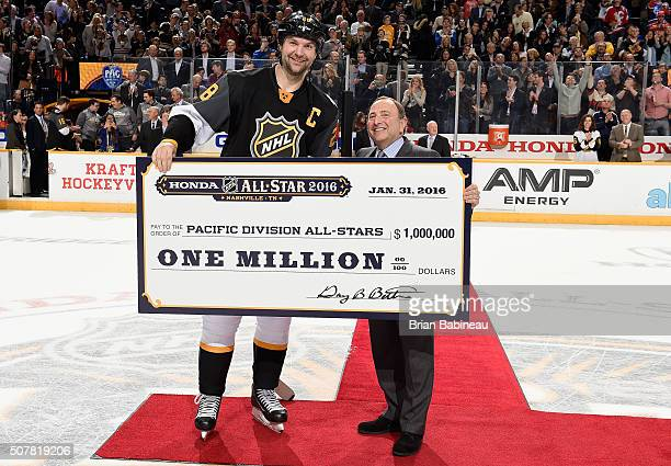 Captain John Scott of the Arizona Coyotes receives the one million dollar winner's check from NHL Commissioner Gary Bettman on behalf of the Pacific...
