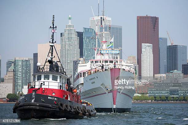 Captain John stands on the bow for the last time as his ship is towed from the Toronto harbour after 40 years