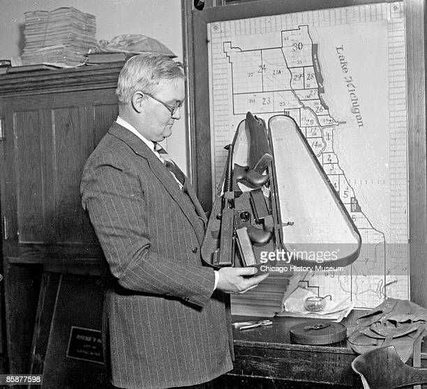 Captain John Stege of the Chicago Police Department holds an open violin case used to hide a machine gun Chicago 1927 A map of Chicago police...