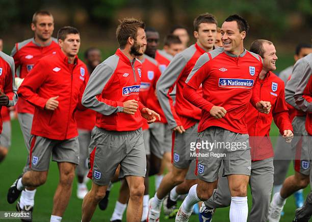 Captain John Terry and David Beckham share a joke as the warm up during the England training session at London Colney on October 6, 2009 in St...