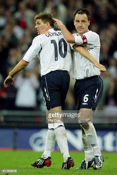 Captain John Terry of England celebrates with Steven Gerrard as he scores their first goal during the international friendly match between England...