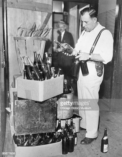 Captain Joseph Goldberg examines contraband beer and booze found in a raid Prohibition and the subsequent illegal trade in alcohol was a catalyst for...