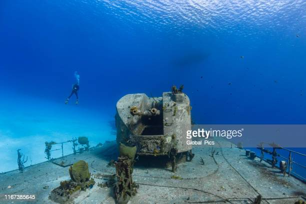 mv captain keith tibbetts shipwreck and diver - cayman brac - machine gun stock pictures, royalty-free photos & images