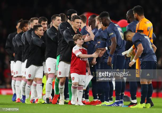 Captain Laurent Koscielny of Arsenal shakes hands with Manchester United players prior to the FA Cup Fourth Round match between Arsenal and...