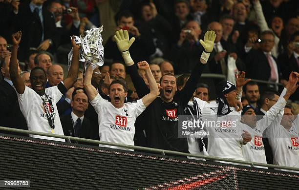 Captain Ledley King of Tottenham Hotspur lifts the trophy with Robbie Keane following victory during the Carling Cup Final between Tottenham Hotspur...