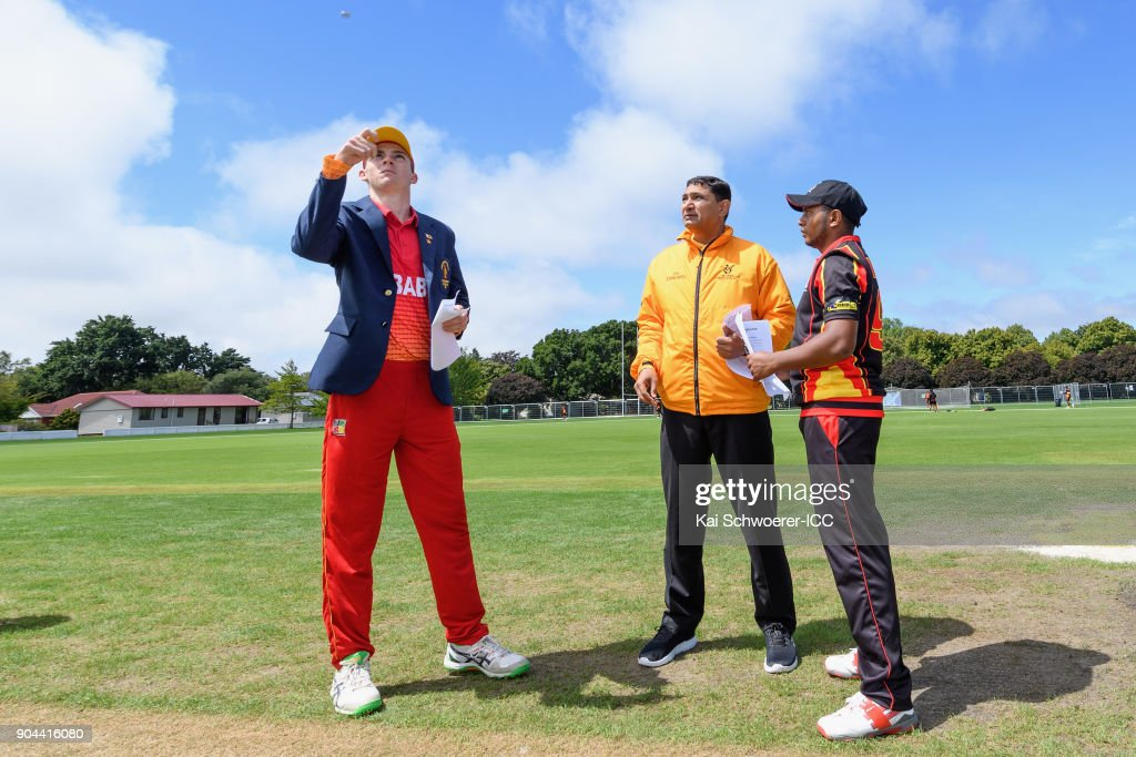 Captain Liam Roche of Zimbabwe, umpire Shozab Raza and captain Vagi Karaho of Papua New Guinea (L-R) take part in the coin toss prior to the ICC U19 Cricket World Cup match between Zimbabwe and Papua New Guinea at Lincoln Green on January 13, 2018 in Christchurch, New Zealand.
