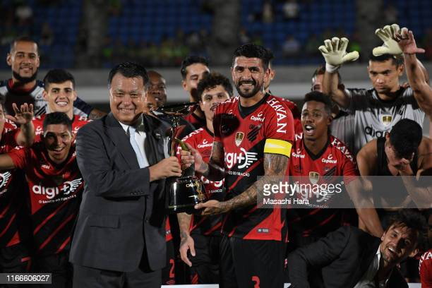 Captain Lucho Gonzales of Atretico Paranaense and Kozo Tashima hold the trophy after the game between Shonan Bellmare and Athletico Paranaense at...