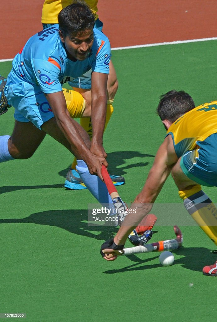 Captain Mark Knowles of Australia (R) tries to block Danish Mujtaba of India during the second semi-final at the men's Hockey Champions Trophy tournament in Melbourne on December 8, 2012. IMAGE STRICTLY RESTRICTED TO EDITORIAL USE - STRICTLY NO COMMERCIAL USE AFP PHOTO / Paul CROCK