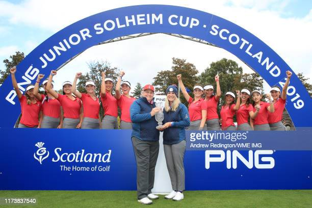Captain Mary Bea Porter and Vice Captain Carly Regains of Team USA pose with the team for a photograph with the Trophy after they win the PING Junior...