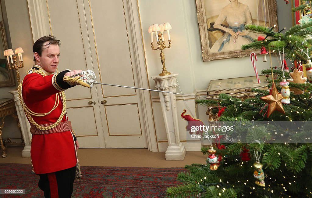 Captain Matthew Wright of the Welsh Guards places decorations with his sword during a reception at Clarence House for children from Helen and Douglas House on December 14, 2016 in London, England. The Duchess of Cornwall, Patron, Helen & Douglas House invited children from the charity and children supported by Roald Dahl's Marvellous Children's Charity to decorate the Christmas tree and join Her Royal Highness for lunch at Clarence House.