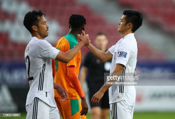 Captain Maya Yoshida of Japan celebrates at the final whistle with goal scorer Naomichi Ueda of Japan at the end of the international friendly match...