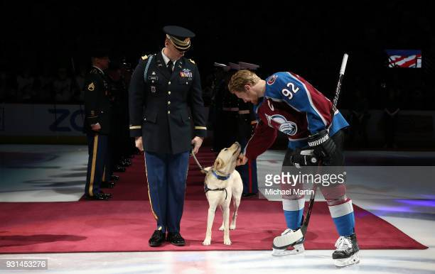 Captain Michael Caspers with his military support dog Vincent drops the puck for the ceremonial faceoff with Gabriel Landeskog of the Colorado...